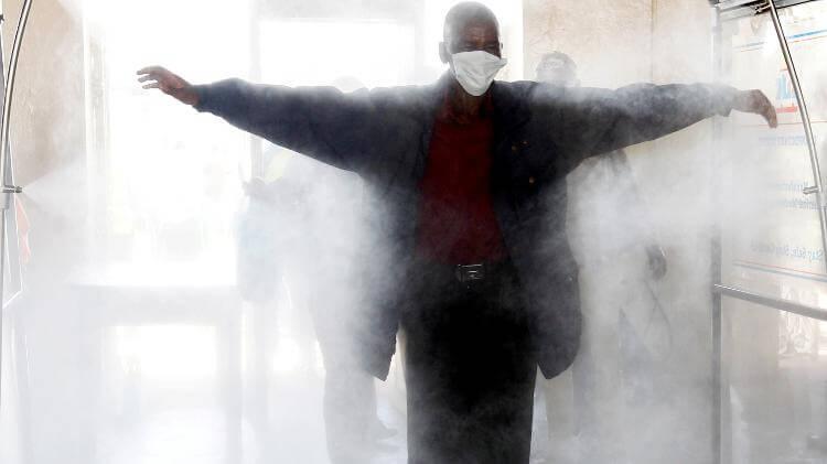 um passageiro caminha atraves de um tunel desinfetante seguindo as regras de distanciamento social - Pragas e Eventos